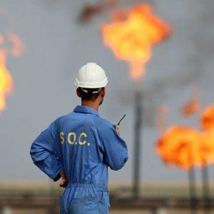 Oil worker in front of oil fields